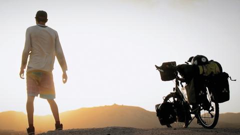 Mann mit Fahrrad in Wüste