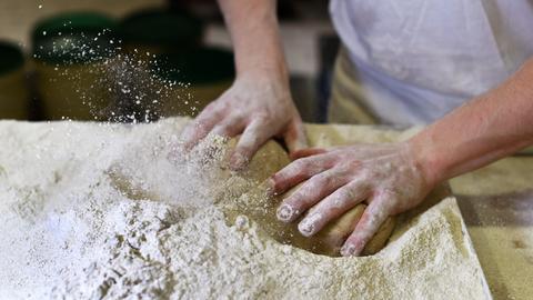 Ein Bäcker knetet Brotteig für Vollkornbrote und wendet sie in Mehl.