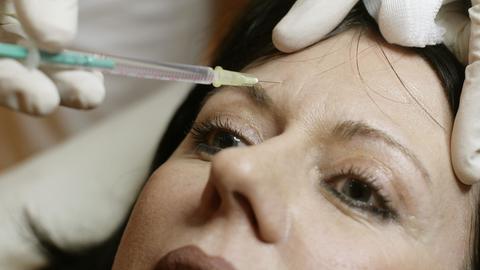 Eine Spritze mit «Botox» hält ein Chirurg einer jungen Frau zu Demonstrationszwecken an die Stirn