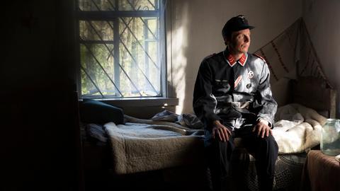 Mann in Unform sitzt auf Bett
