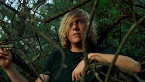 Mann steht im Wald