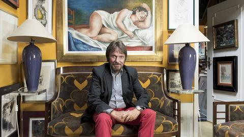 Frank Brabant sitzt in seiner Wohnung inmitten der von ihm gesammelten Kunstwerke.
