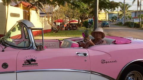 Ältere Frau in pinkfarbenem Oldtimer
