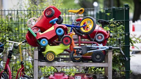 Bobby-Cars, andere Spielautos und Gefährte für Kinder liegen angeschlossen vor einer Kita.