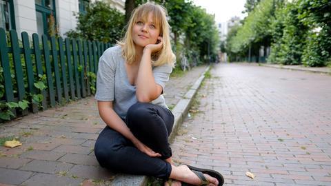 Junge Fraus sitzt auf Boden