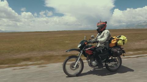 Frau auf Motorrad in weiter Landschaft