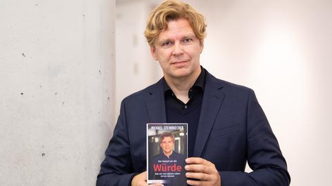 """Michael Steinbrecher, Buchautor und TV - Journalist, steht mit seinem Buch in der Hand im Foyer des Bildungszentrums Hospitalhof in Stuttgart. Steinbrecher stellt sein neues Buch """"Der Kampf um die Würde"""" vor."""