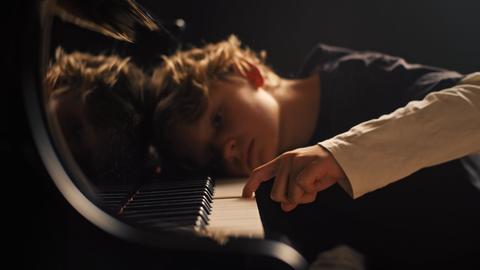 Junge liegt mit Kopf auf Klaviertastatur und schlägt einen Ton an.