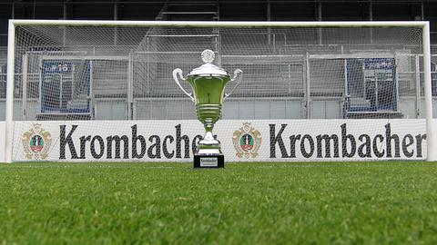 Der Hessenpokal steht auf dem Rasen vor einem Tor. Im Hintergrund leere Ränge.