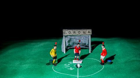 """Tippkick-Spieler auf einem Spielfeld mit dem Schriftzug """"Corona"""""""