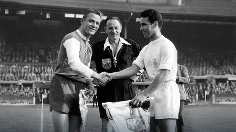 Eintracht-Spieler Alfred Pfaff (links) und Zarraga von Real Madrid (rechts) schütteln sich vor dem Spiel die Hände und tauschen Wimpel aus.