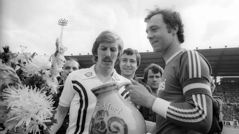 Franz Beckenbauer (re., FC Bayern München) bekommt von Jürgen Grabowski (Frankfurt) zum Abschied einen Weinkrug geschenkt.