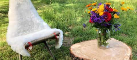 Selbstgebaute Gartenmöbel aus knorrigem Holz: ein Stuhl mit Lammfell und ein kleiner Beistelltisch