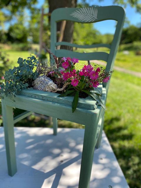 Grün angestrichener, großer bepflanzter Stuhl.
