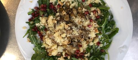 Sommerlicher Pilz-Salat mit Rucola, Parmesan und Granatapfelkernen.