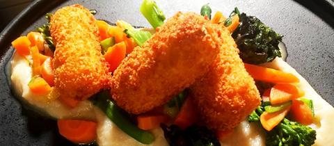 Drei Couscous-Kroketten auf Topinamburpüree mit Karotten und Bimi angerichtet.