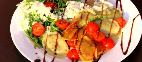 Ein Teller mit bunten Ravioli und Rucola.