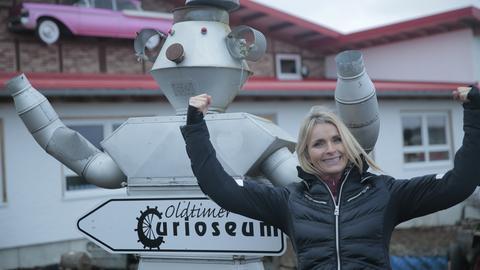 Susanne Barfuß mit einem Blech-Roboter vor dem Curioseum.