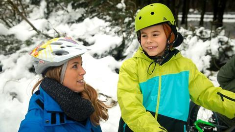 Reporterin Rebecca Rühl und ein Kind bei einer Radtour im Schnee.
