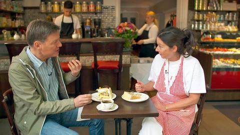 Dieter Voss mit Anja Klügling, der Besitzerin des Cafés Merci in Bad Soden, beim Probieren der berühmten hauseigenen Hundertwasser-Torte.