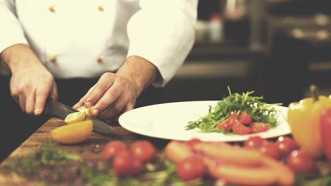 Ein Koch schneidet Gemüse auf einem Holzbrett.