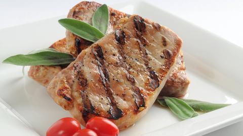 Schweinekoteletts mit Salbei und kleinen Tomaten garniert.