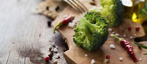 Frischer Brokkoli, Chilischoten und Öl auf Holztisch.