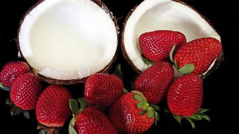 Erdbeeren und eine halbierte Kokosnuss.