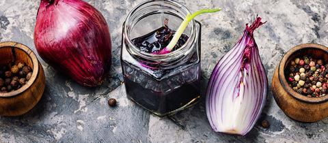Rote-Zwiebel-Marmelade im Gläschen, mit aufgeschnittener roten Zwiebel und Döschen von Pfefferkörnern nebendran.