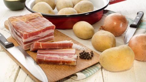 Kartoffel, Zwiebel und Speck auf einem Brett.
