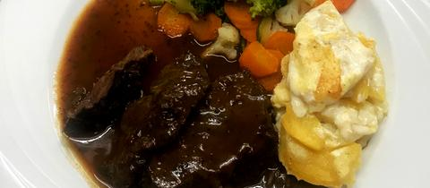 Ochsenbacke auf Zwetschgensoße mit Rahmkartoffeln und Brokkoligemüse.