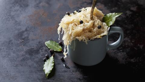 Sauerkraut mit Lorbeer-Blättern und Wacholder-Beeren in eine überquellenden Tasse.