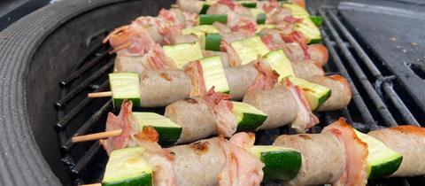 Bratwurst-Spieße mit Gemüse auf Grill.