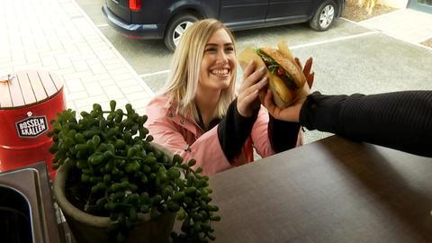Eine Frau holt sich an einem Foodtruck einen Burger