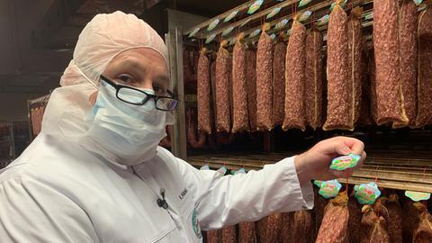 Mitarbeiter des Fleischwerk bei der Produktion und bei der Kontrolle