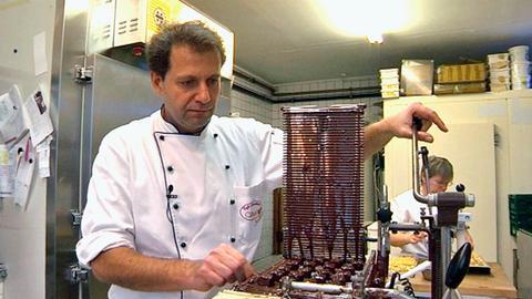 Andreas Vogel beim Überziehen von Pralinen mit Schokolade.