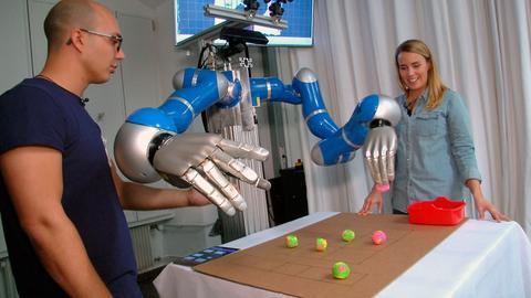 """Moderatorin Rebecca Rühl mit Rudolf Lioutikov am zweihändigen Robotersystem im """"Roboter-Lernlabor"""" der Technischen Universität Darmstadt."""