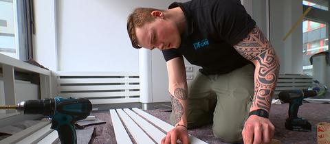Ein Handwerker misst ein Regal aus.