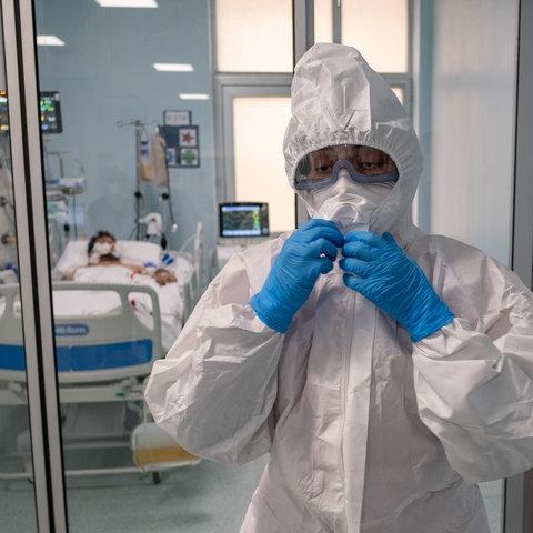 Eine Ärztin in Schutzkleidung vor einem Patientenzimmer