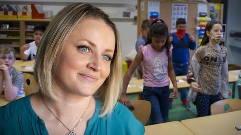 Frau im Klassenraum, im Hintergrund spielen Kinder.