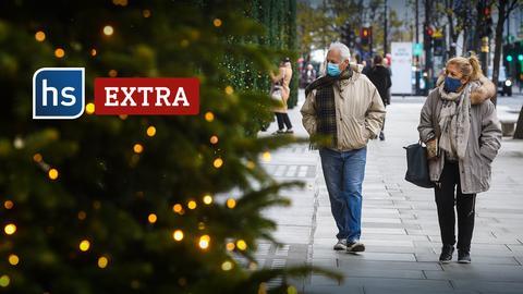 Menschen mit Maske laufen an einem Weihnachtsbaum entlang.