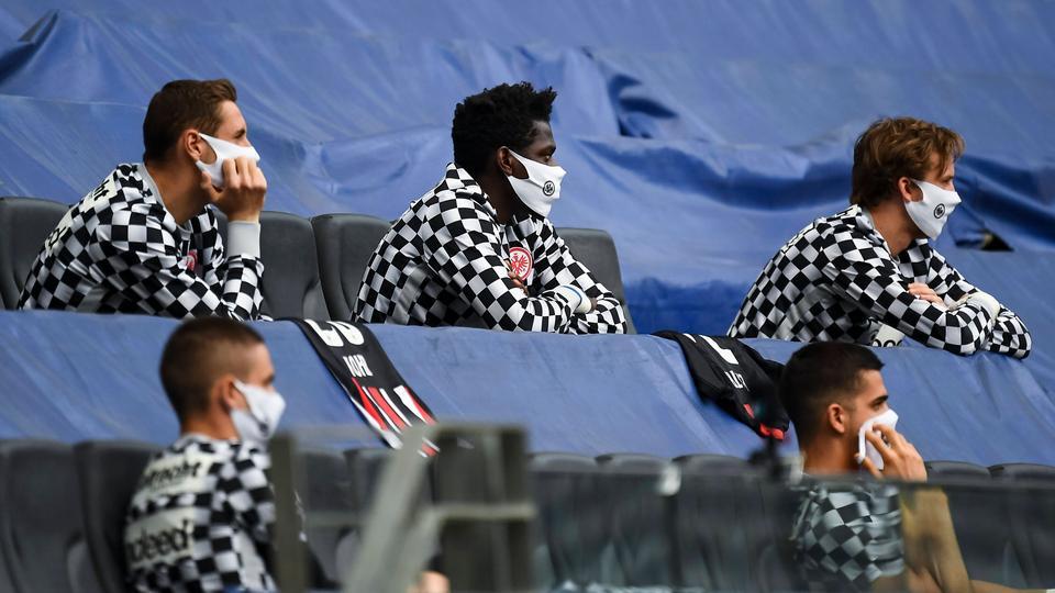 Mehrere Eintracht Frankfurt-Spieler sitzen auf einer leeren Tribüne verteilt, mit Masken geschützt.