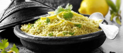 Couscous mit Zitronen und Koriander in einem Behältnis angerichtet.