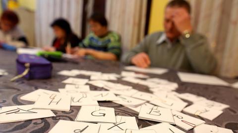 Erwachsene sitzen vor Buchstabenkärtchen an einem Tisch.