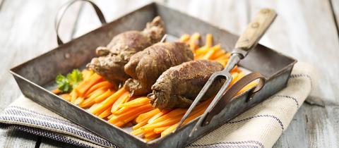 Drei Rouladen liegen auf Karottengemüse in einem blechernen Tablett auf holzigem Untergrund.