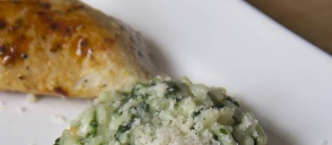Risotto mit Parmesan und Hähncenbrust auf einem weißen Teller.