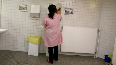 Eine Putzfrau füllt in einer öffentlichen Toilette den Papierbehälter auf.