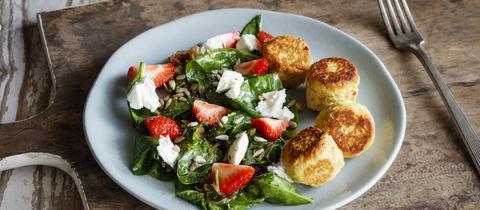 Ein Teller mit Spinatsalat und Falafel, Ziegenkäse, Erdbeeren und Sonnenblumenkernen.