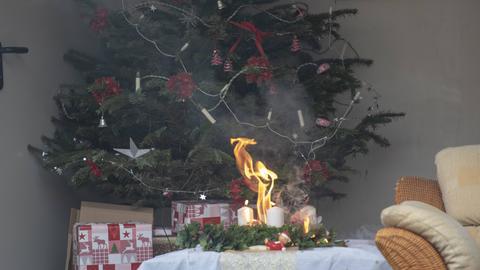 Ein brennender Adventskranz steht auf einem Wohnzimmertisch vor einem geschmückten Weihnachtsbaum.