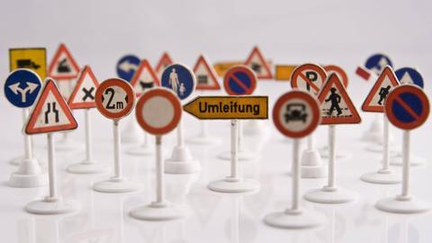 Viele kleine deutsche Modell-Verkehrrschilder auf weißem Untergrund.